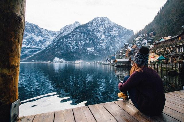žena sedící u horského jezera
